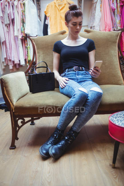 Woman using mobile phone in boutique store — Stock Photo