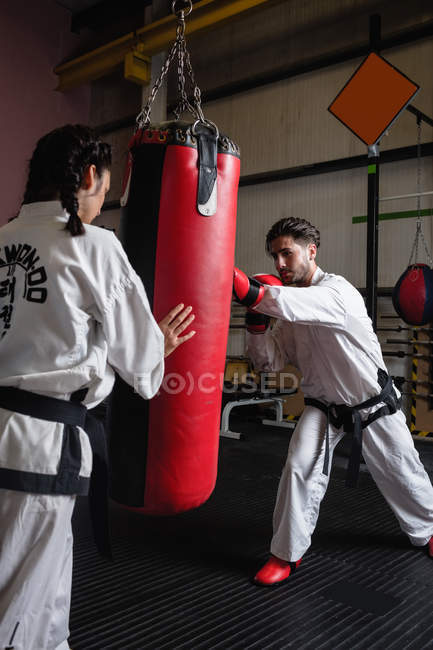 Sportlerin und Sportler beim Karate mit Boxsack im Studio — Stockfoto
