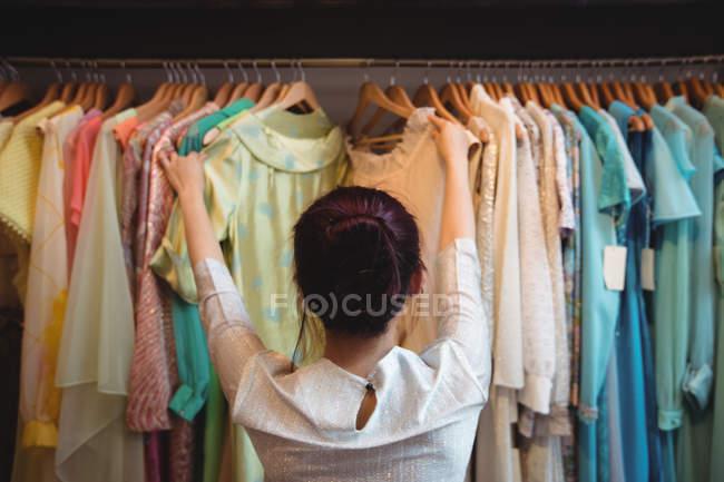 Donna che sceglie un abbigliamento dall'appendiabiti al negozio boutique — Foto stock