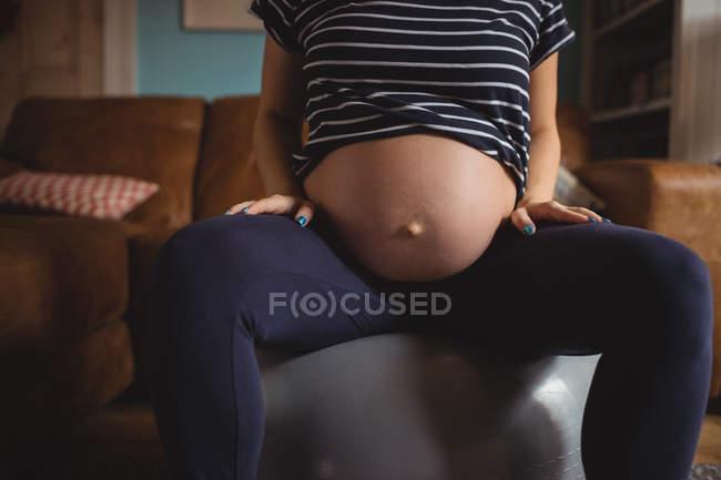 Мидсекция беременной женщины, сидящей на мяче в гостиной дома — стоковое фото