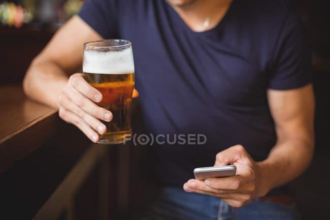 Середині розділі людини за допомогою мобільного телефону, маючи келих пива в м. бар — стокове фото