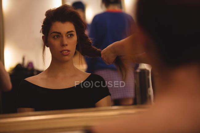 Отражение красивая женщина на зеркале укладки волосы в салоне — стоковое фото