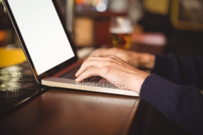 Mid section of man using laptop at bar counter — Stock Photo