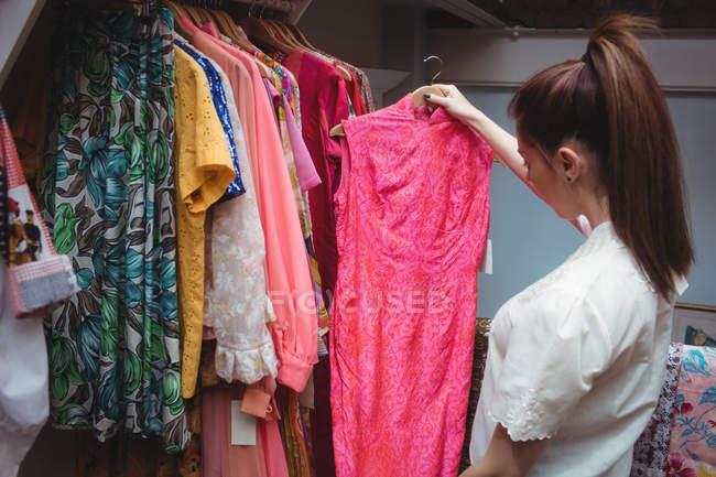 Donna che seleziona un vestiti sul gancio presso negozio di abbigliamento — Foto stock
