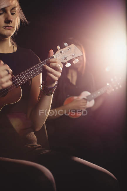 Beautiful women playing a guitar in music school — Stock Photo