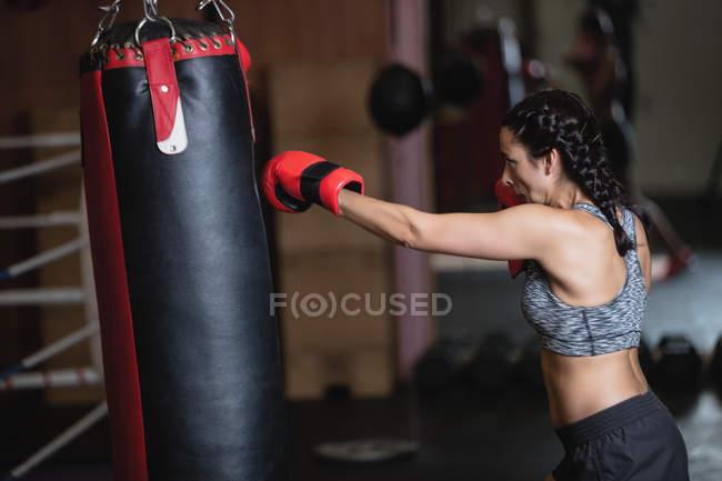 Vista laterale del pugile femminile che pratica boxe con sacco da boxe in palestra — Foto stock