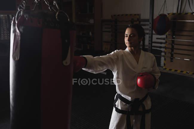 Donna che pratica karate con sacco da boxe in palestra — Foto stock