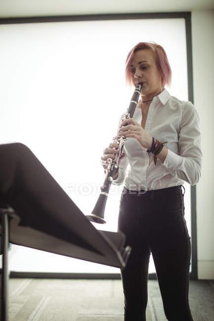 Schöne Frau spielt Klarinette in der Musikschule — Stockfoto