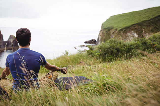 Rear view of man performing yoga on cliff — Stock Photo