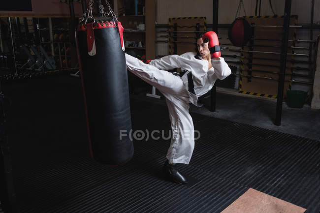 Sportliche Frau übt Karate mit Boxsack im Fitnessstudio — Stockfoto