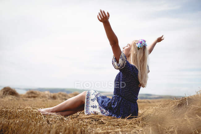 Беззаботная блондинка сидит в поле с поднятыми руками — стоковое фото