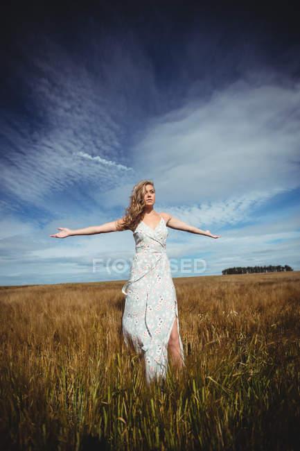 Женщина, стоящая с распростертыми руками на пшеничном поле в солнечный день — стоковое фото
