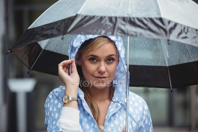Портрет красива жінка тримає парасольку під час сезону дощів і, дивлячись на камеру — стокове фото