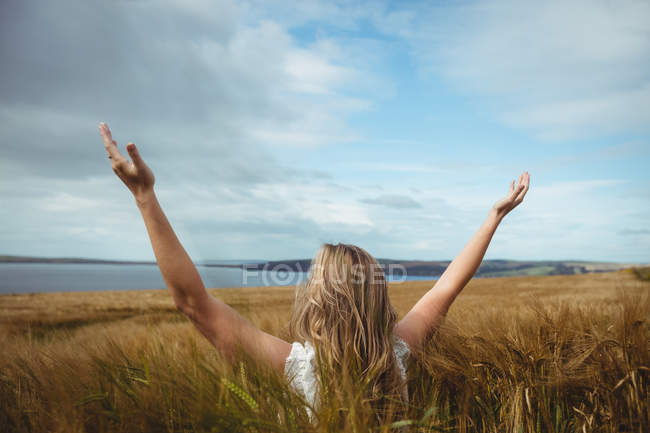 Rear view woman standing with raised hands in field — Stock Photo