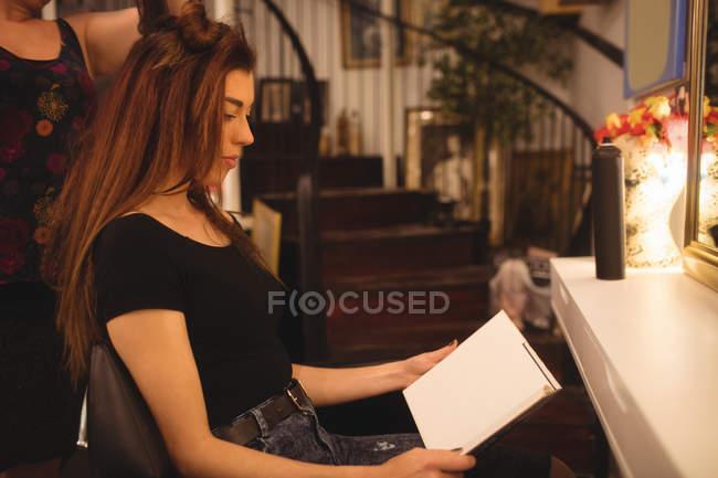 Женщина, чтения журнала при укладке волосы в салоне — стоковое фото