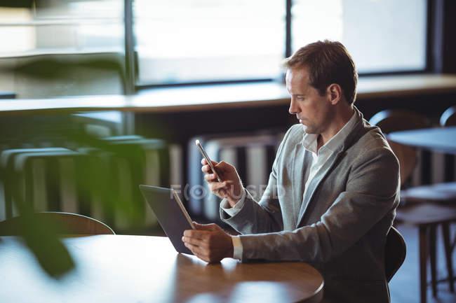 Uomo d'affari concentrato utilizzando tablet digitale e telefono cellulare in caffè — Foto stock