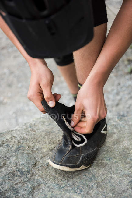 Male hiker tying shoelaces in forest — Stock Photo