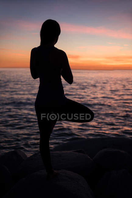 Rear view of Woman performing yoga on rock during beautiful sunset — Stock Photo