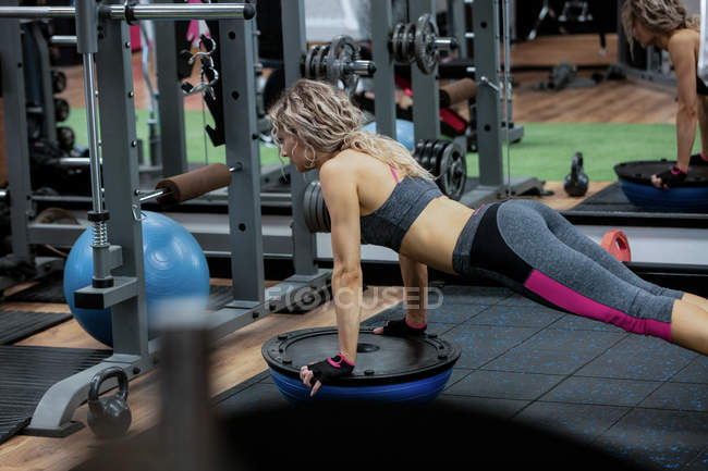 Woman doing push-up on bosu ball in gym — Stock Photo