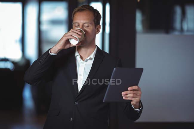 Entreprise ayant le café tout en utilisant la tablette numérique de bureau — Photo de stock