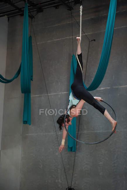 Gymnast performing gymnastics on hoop in fitness studio — Stock Photo