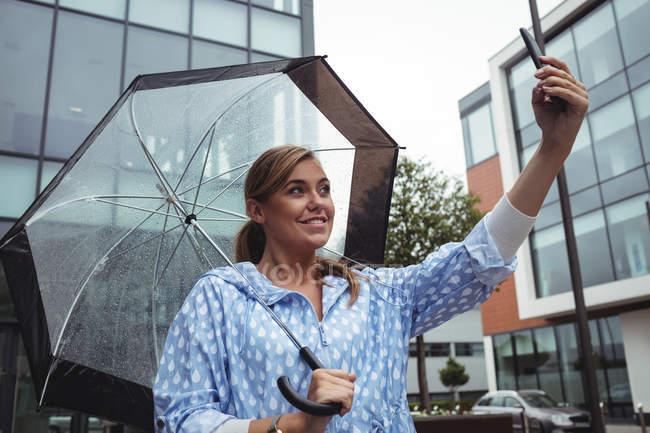Belle femme tenant parapluie tout en prenant selfie pendant la saison des pluies — Photo de stock