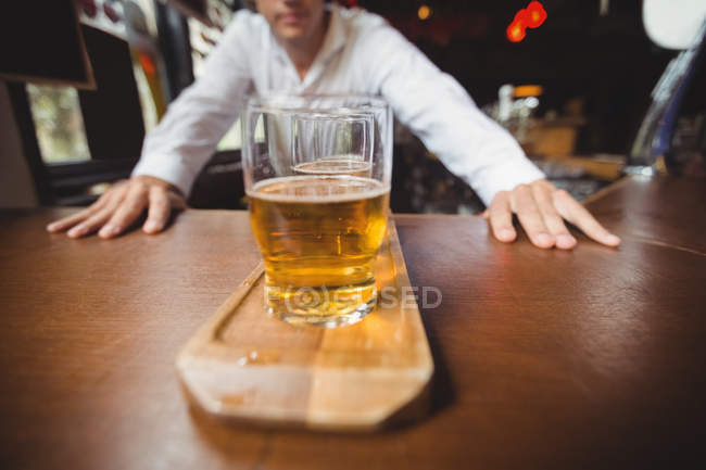 Бармен, стоя возле счетчик с бокалов пива в баре — стоковое фото