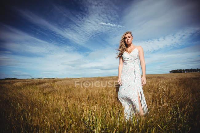 Nachdenkliche Frau steht an sonnigem Tag im Weizenfeld — Stockfoto