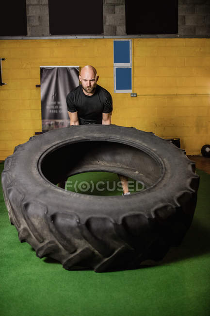 Handsome sportsman lifting heavy tire in gym — Stock Photo