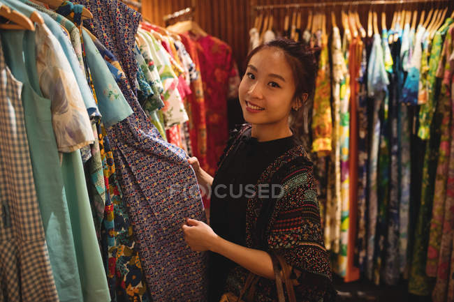Ritratto di donna sorridente che seleziona i vestiti sui ganci presso negozio di abbigliamento — Foto stock