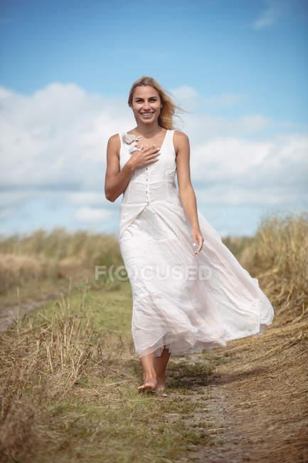 Attraktive lächelnde blonde Frau, die auf Pfad in Feld geht — Stockfoto