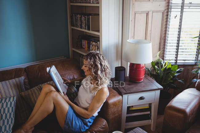 Beautiful woman reading magazine in living room at home — Stock Photo