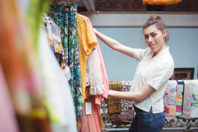 Portrait of woman selecting a clothes on hanger at apparel store — Stock Photo