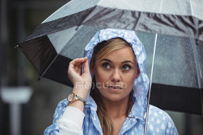 Вдумчивый женщина, держащая зонтик в дождливую погоду — стоковое фото