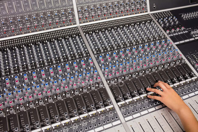 Hand of a female student using sound mixer in a studio — Stock Photo