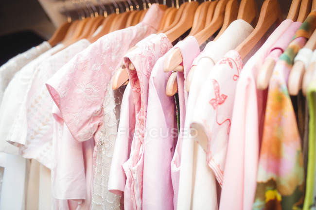 Various colorful clothes on a hangers at boutique store — Stock Photo