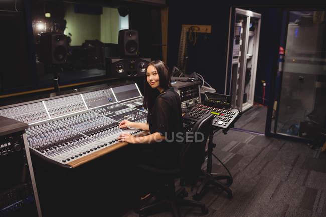 Студентка использует звуковой микшер в студии — стоковое фото