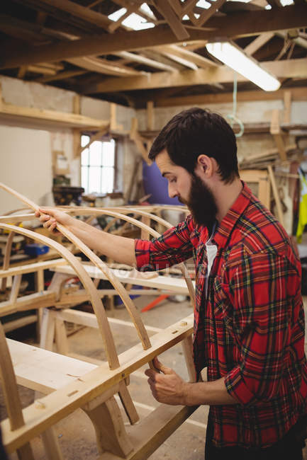 Man Preparing A Wooden Boat Frame At Boatyard One Person Casual