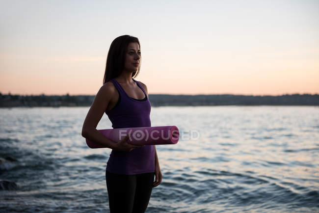 Красивая женщина, стоя с мат для йоги на пляже в сумерках — стоковое фото