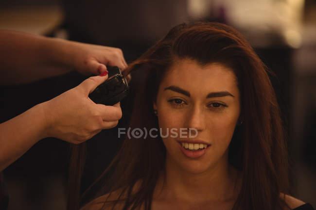 Женщина, как волосы выпрямить в салоне волосы — стоковое фото