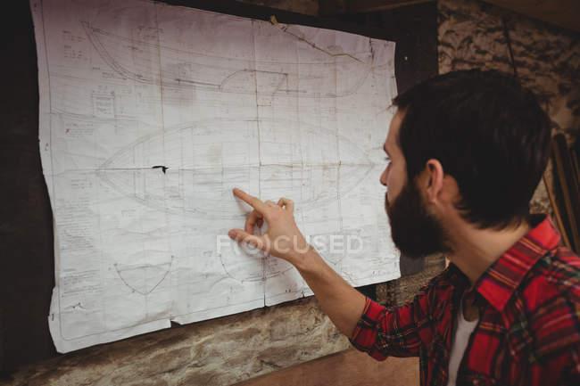 Man looking at blueprint on boatyard wall — Stock Photo