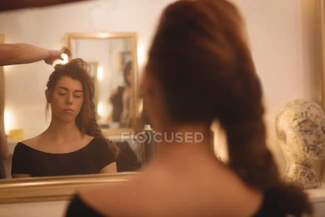 Reflet d'une belle femme sur miroir coiffer ses cheveux au saloon — Photo de stock