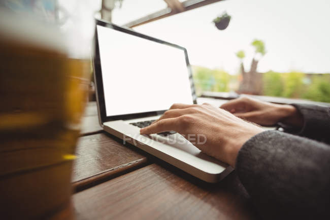 Close-up of man using laptop in bar — Stock Photo