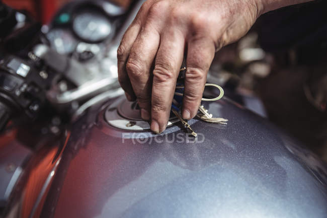 Hand of mechanic closing a fuel tank of motor bike at workshop — Stock Photo