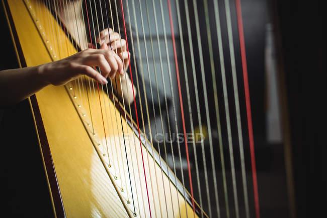 Mittelteil einer Harfenspielerin in Musikschule — Stockfoto