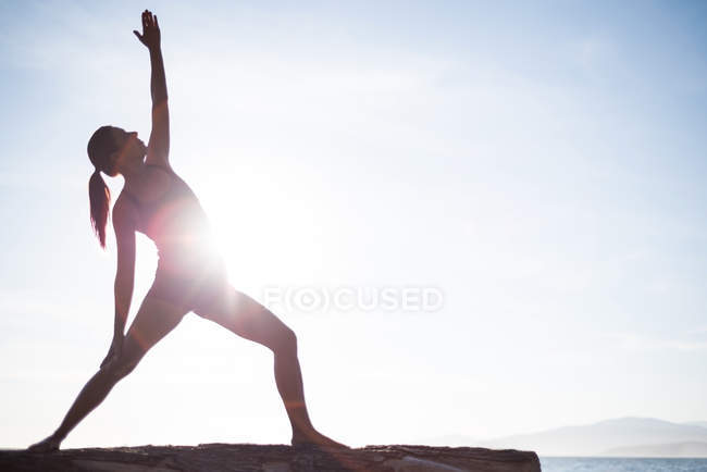 Вид спереди женщины, занимающейся йогой на капельницах в солнечный день — стоковое фото