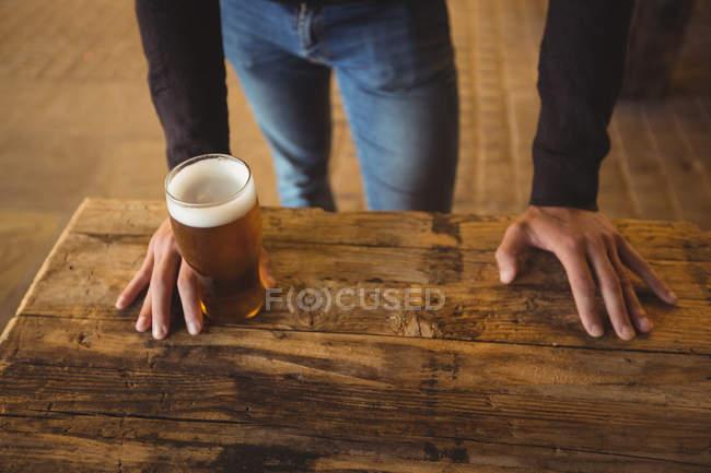 Hombre con vaso de cerveza en el bar - foto de stock