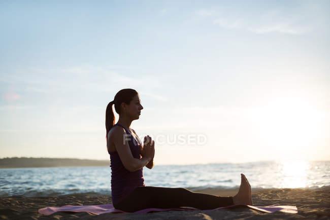 Вид сбоку на женщину, практикующую йогу на пляже в солнечный день — стоковое фото