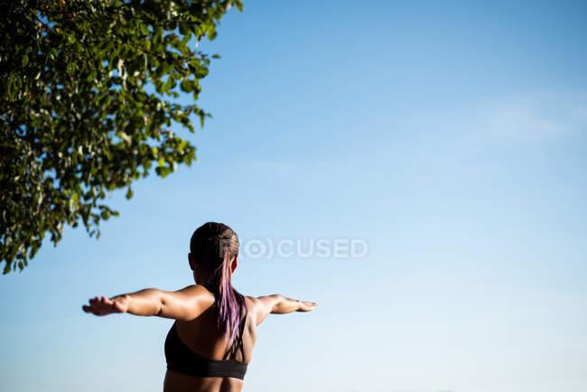 Visão traseira da mulher praticando ioga no jardim no dia ensolarado — Fotografia de Stock
