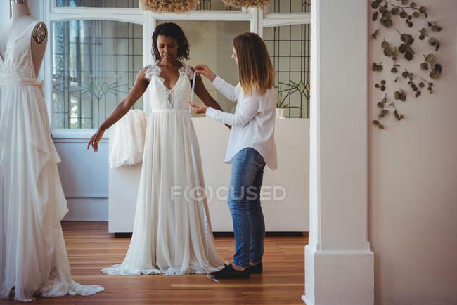 Female fashion designer taking measure of woman in studio — Stock Photo